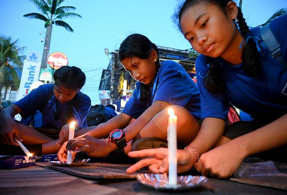 Schoolchildren light candles during a memorial service for the victims of the 2002 Bali bombings to mark the 17th anniversary of the attacks in Kuta near Denpasar on Bali island October 12, 2019. — AFP pic