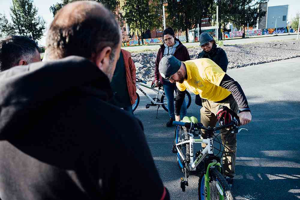 Sami (front right), one of the teachers of the Let's Ride project, shows the different parts of the bicycle to a group of immigrants, in Merihaka area in Helsinki. — AFP pic