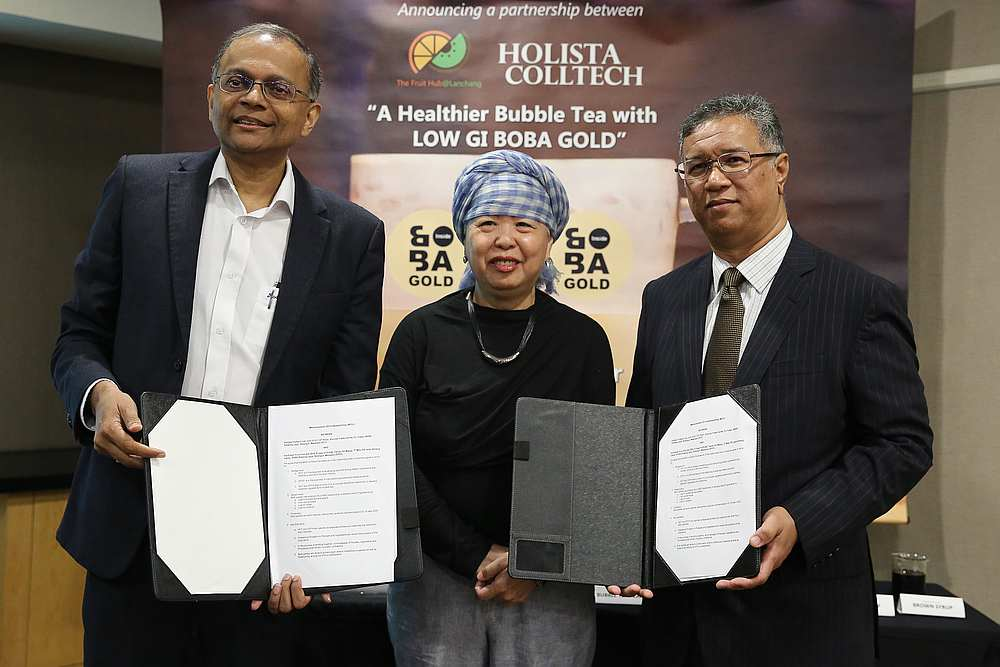 Holista CEO Datuk Dr Rajen Manicka and Fruit Hub chairman Mohamed Zainurin Mohamed Zain exchanging joint collaboration documents. Looking on is SunFresh managing director Foong Wai Fong. — Picture by Mohd Yusof Mat Isa