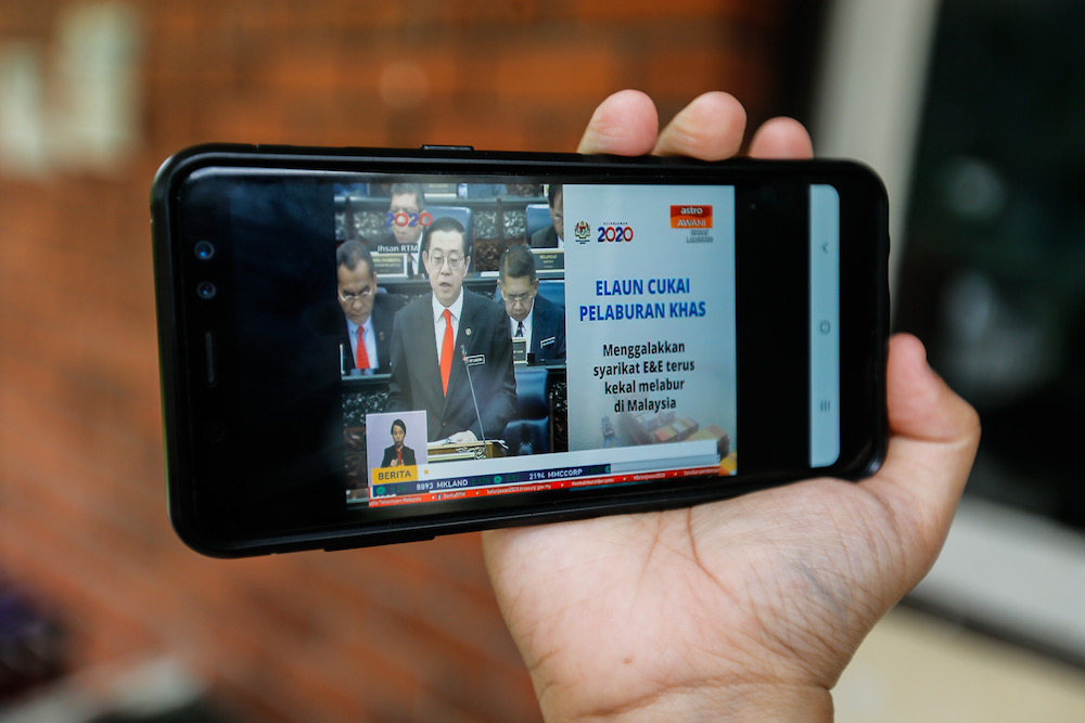 Noor Wahida Baba Din watches the Budget 2020 speech by Finance Minister Lim Guan Eng 'live' on the phone at home in Bukit Gelugor October 11, 2019. — Picture by Sayuti Zainudin