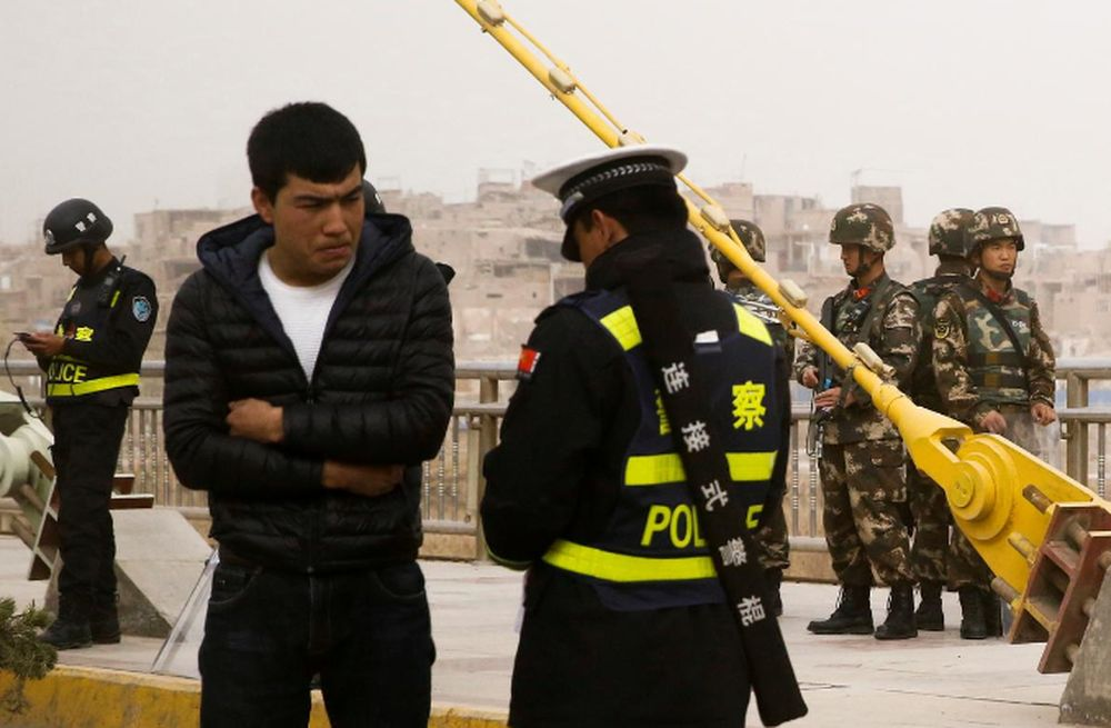 File picture shows a police officer checking the identity card of a man as security forces keep watch in a street in Kashgar, Xinjiang Uighur Autonomous Region, China, March 24, 2017. — Reuters pic