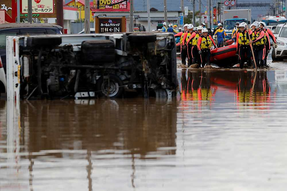 Rescue workers carry a rubber dinghy past an overturned car as they search a flooded area in the aftermath of Typhoon Hagibis in Nagano Prefecture, Japan October 14, 2019. — Reuters pic