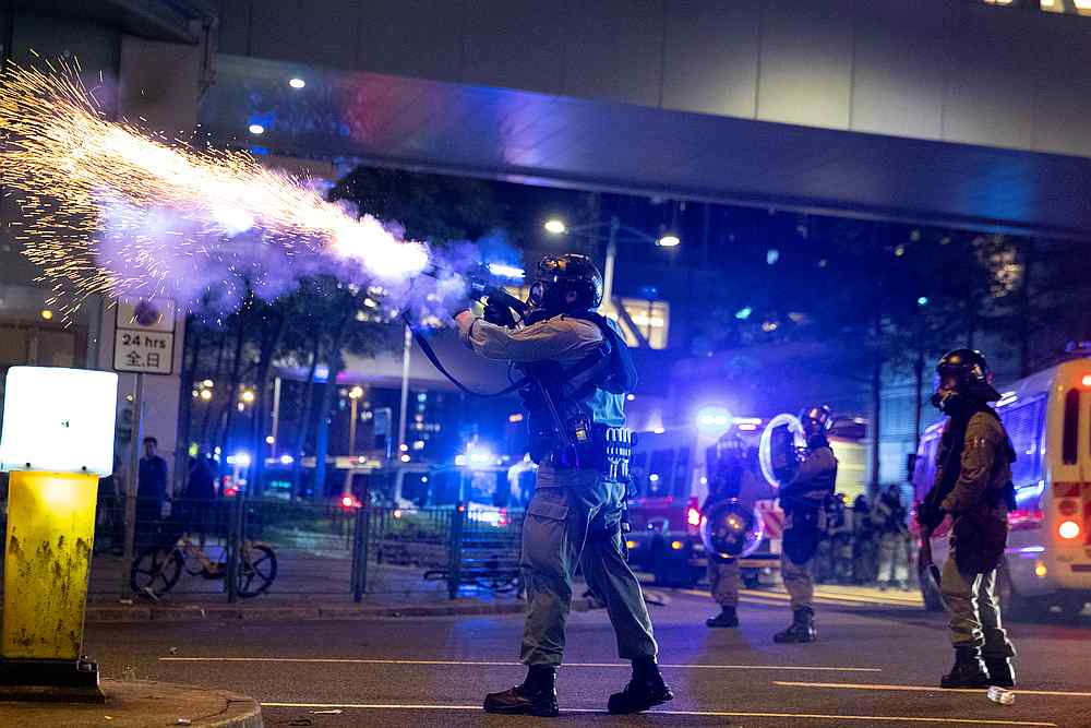 A riot police officer fires a tear gas canister toward anti-government protesters during a demonstration in the Tseung Kwan O residential area in Kowloon, Hong Kong October 7, 2019. — Reuters pic