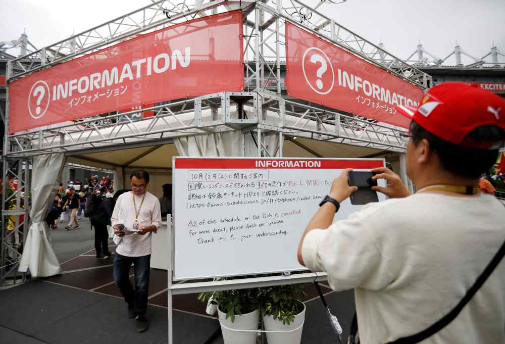 A spectator takes photos of an information board announcing the cancellation of all practice and qualifying sessions scheduled for tomorrow due to the approach of Typhoon Hagibis, at Formula One Japanese Grand Prix in Suzuka October 11, 2019. ― Reuters pic