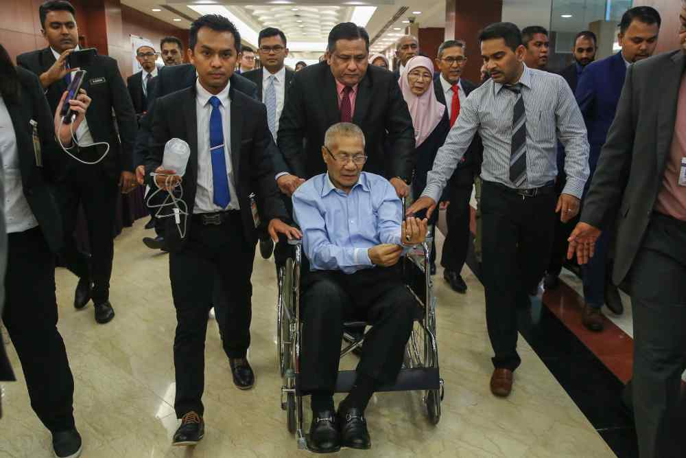 Nibong Tebal MP Datuk Mansor Othman is taken out on a wheelchair after he collapsed during the debate in Dewan Rakyat October 21, 2019. ― Picture by Yusof Mat Isa