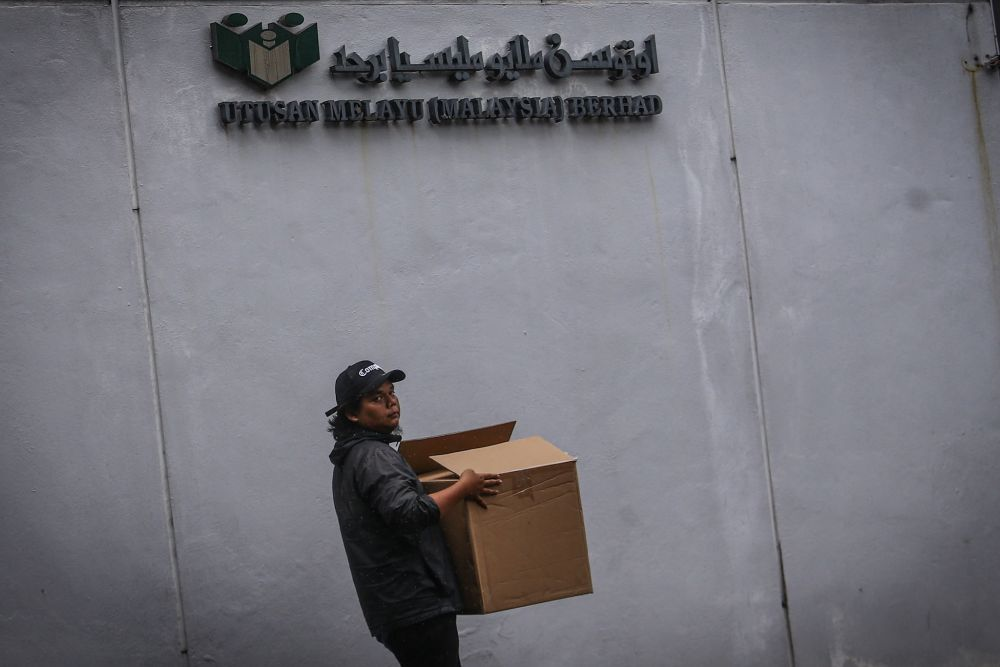 An employee is seen leaving the Utusan Melayu building with his belongings after the newspaper ceased operations on October 9, 2019. — Picture by Hari Anggara