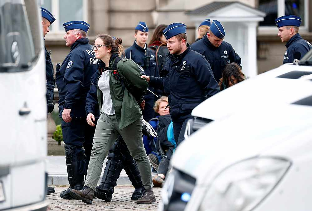 Belgian police officers detain a climate activist in front of the Royal Palace during the Extinction Rebellion protest in Brussels, Belgium October 12, 2019. — Reuters pic