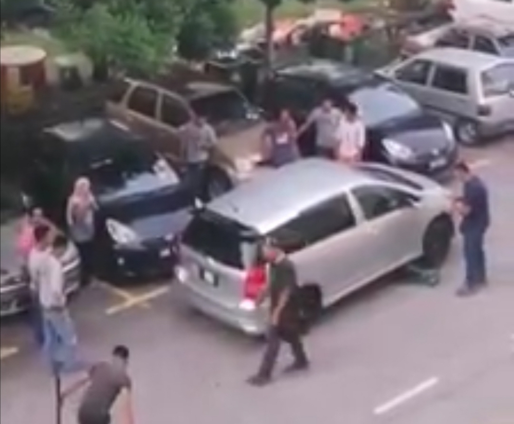 Teamwork is everything for this group of men helping move the inconsiderately double parked car. — Facebook/ We are Malaysians