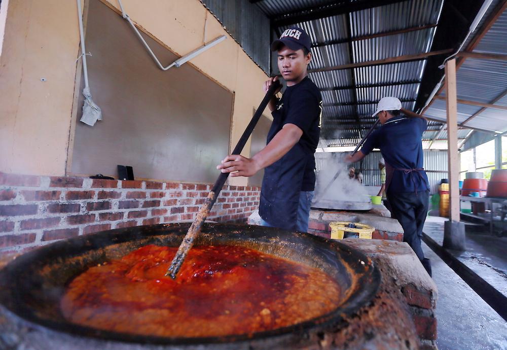 A man cooks rendang tok in Kampung Pasir Putih. — Picture by Farhan Najib