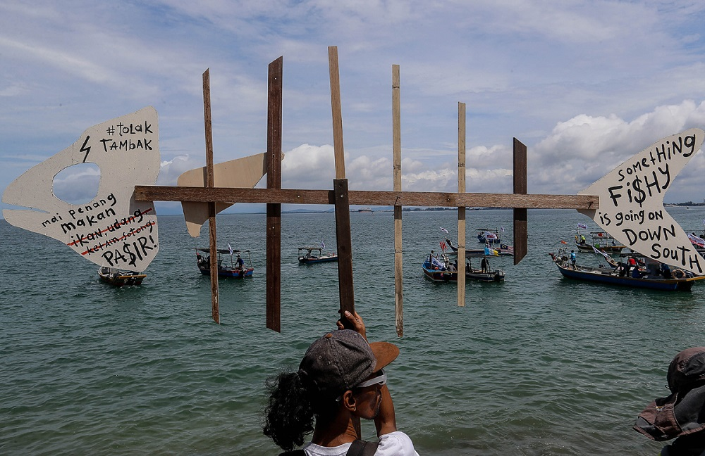 A man holds a signboard in protest against the proposed Penang South Reclamation project at the Esplanade November 4, 2019. — Picture by Sayuti Zainudin