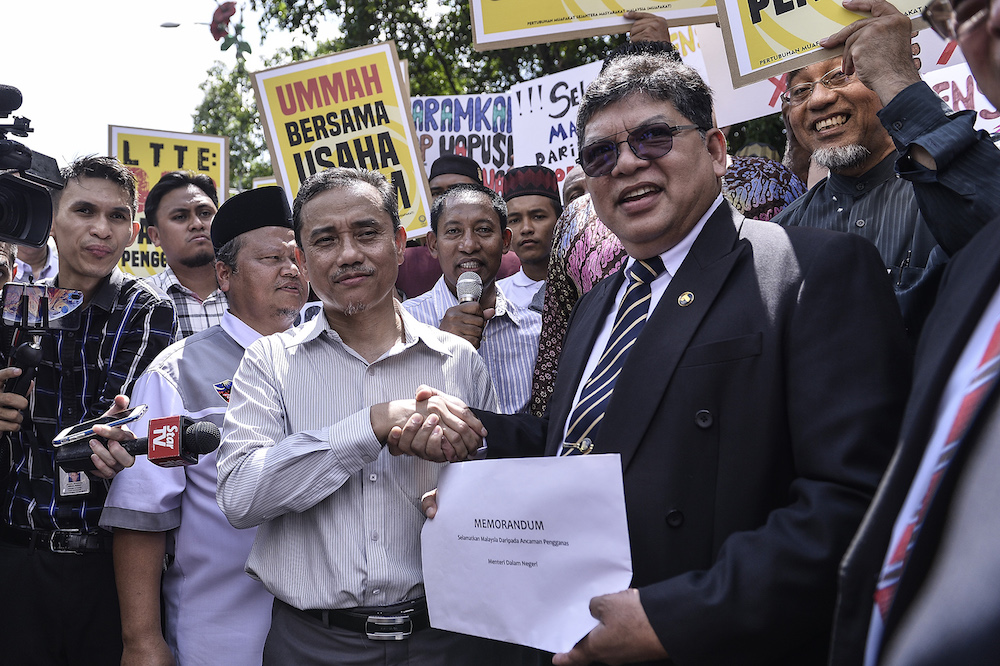 PKR chief whip Datuk Johari Abdul accepts a memorandum on behalf of Pakatan Harapan from Ummah chairman Aminuddin Yahaya in front of Parliament November 5, 2019. — Picture by Miera Zulyana