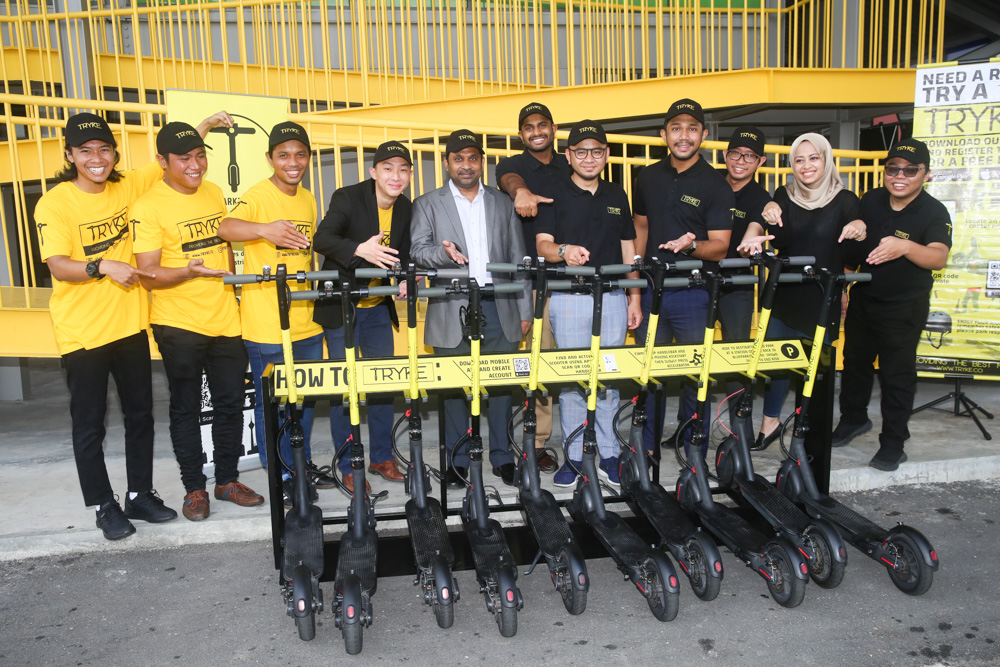Tryke founder Timothy Wong (fourth left) and co-founder Shazwan Abdul Razak (fifth right) along with their staff pose for a group picture during the TRYKE e-scooter soft launch at RekaScape in  Cyberjaya November 22 2019 . — Pictures by Choo Choy May