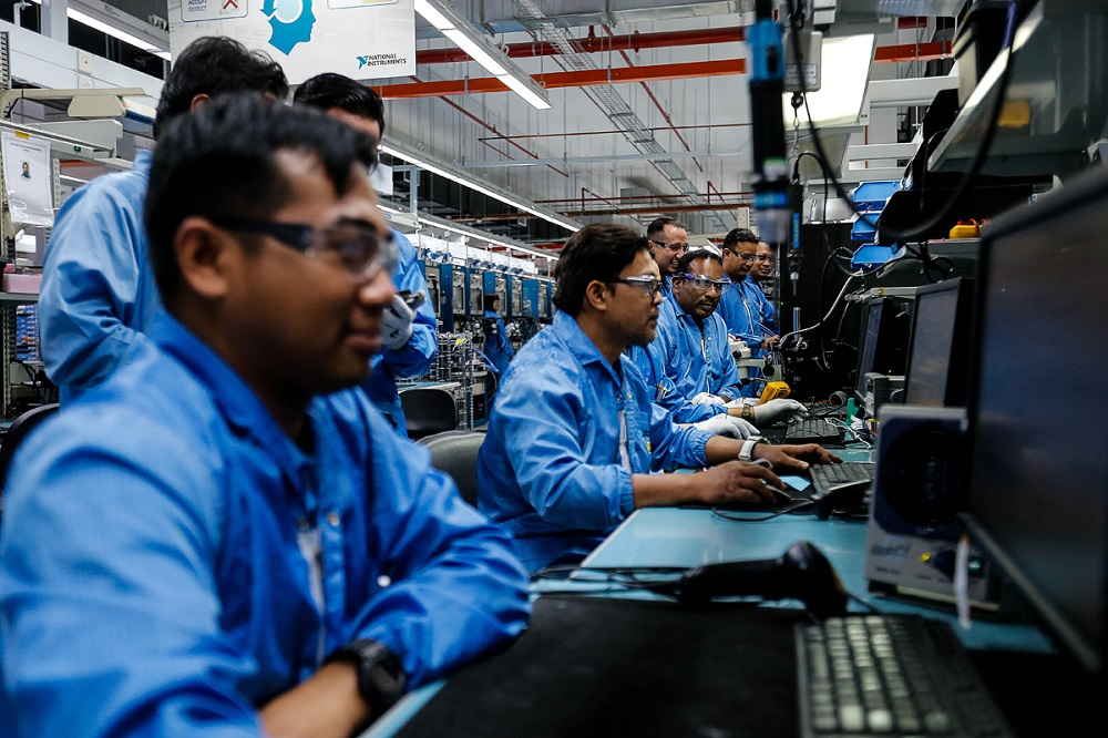 Workers are pictured at their respective stations at a factory in Batu Maung. — Picture by Sayuti Zainudin