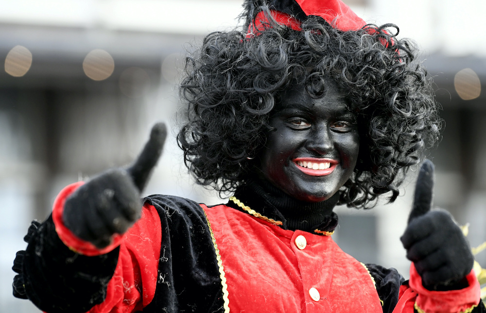 An assistant of Saint Nicholas called 'Zwarte Piet' (Black Pete) gestures as they arrive by boat at the harbour of Scheveningen, Netherlands, November 16, 2019. — Reuters pic