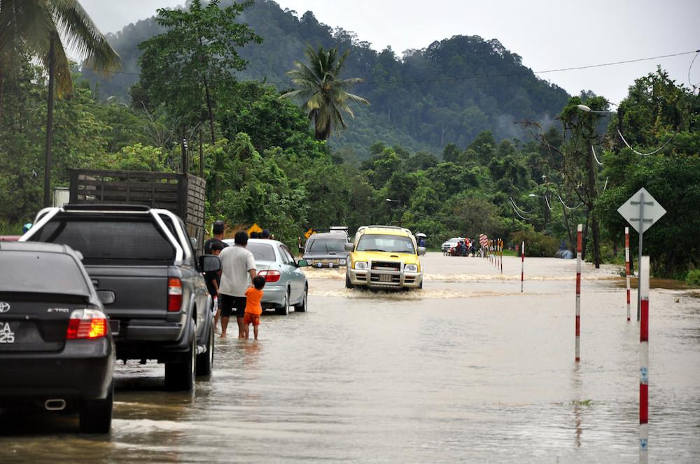 Cars navigate a flooded road at Kampung Gertak Jerubun in Pasir Akar, Terengganu November 29, 2019. — Bernama pic