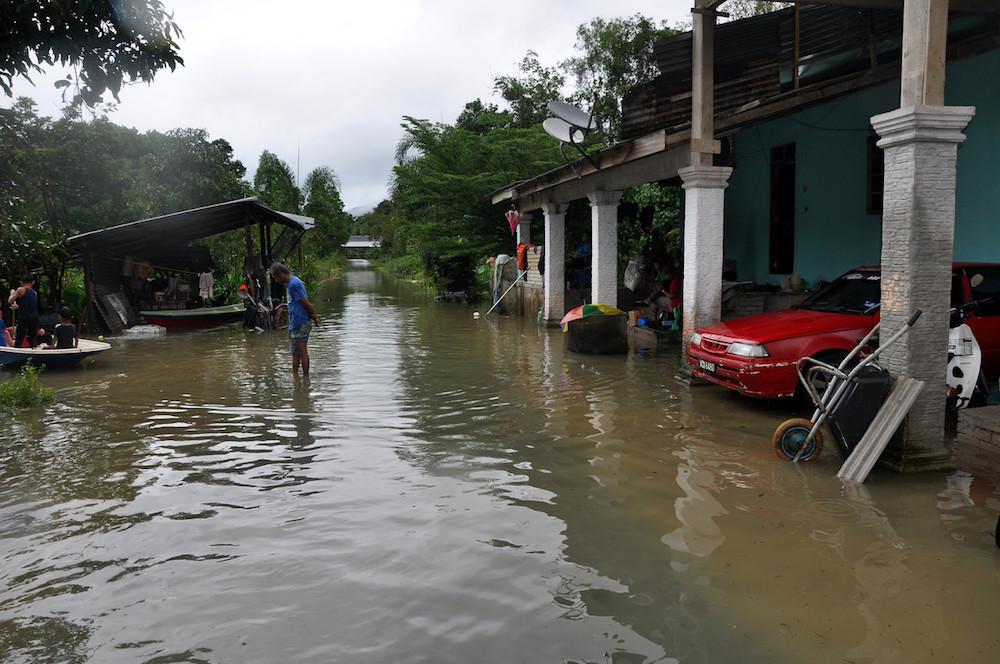 A man wades in calf-deep water in a flooded residential area at Kampung Lepan Kejor in Jerteh, Terengganu November 29, 2019. — Bernama pic