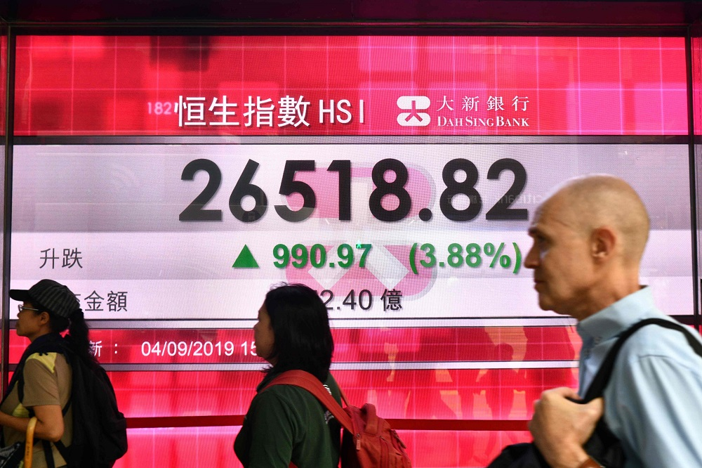 Pedestrians walk past a stocks display panel showing activity of the Hang Seng Index in Hong Kong September 4, 2019. — AFP pic