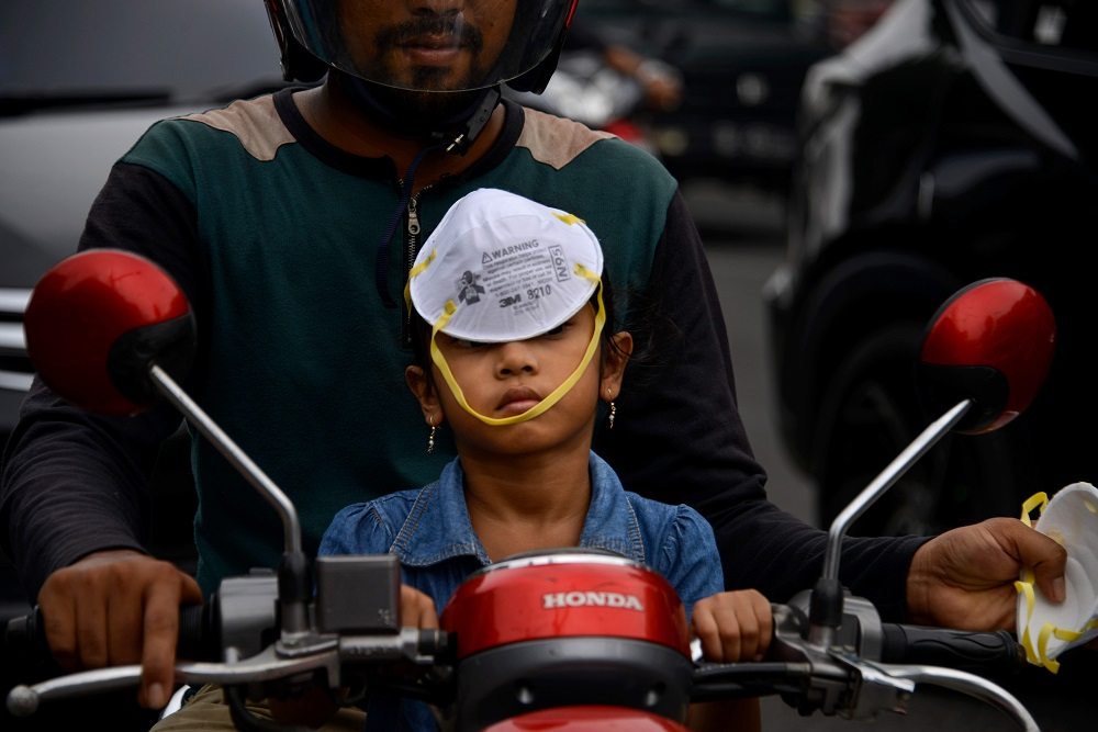 A child wears a facemask on her head as a thick haze blankets the sky over Banda Aceh on September 24, 2019, caused when Indonesian farmers use illegal slash-and-burn techniques to clear land for agriculture, spewing toxic haze across Southeast Asia. — AFP pic