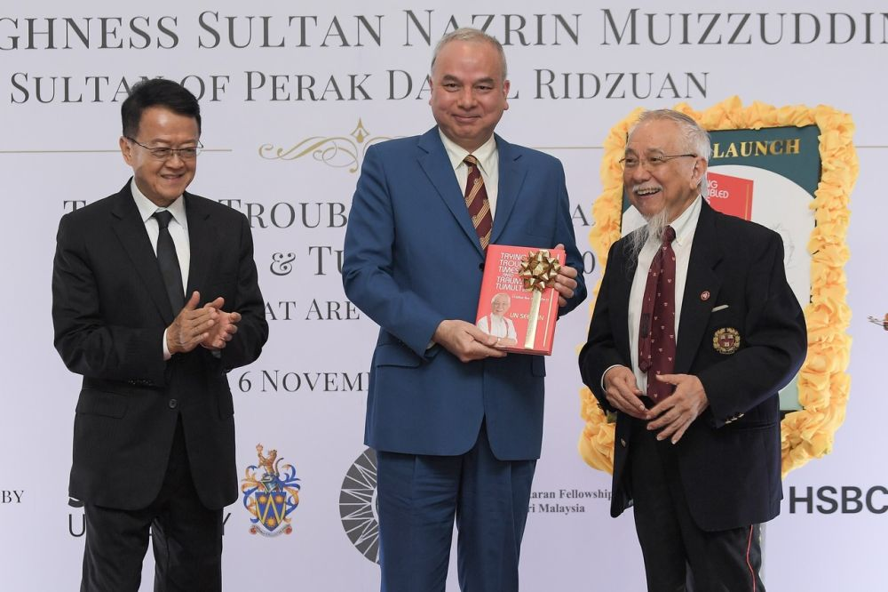 Sultan Nazrin Muizzuddin Shah poses with a copy of Tan Sri Lin See-Yan's (right) book, 'Trying Times Amid Tumult and Trauma' November 6, 2019. — Bernama pic