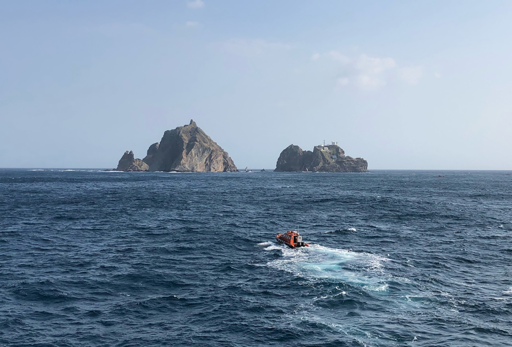 This handout photo taken November 1, 2019 and provided by the Korea Coast Guard shows rescue members searching for missing people after a helicopter crashed into the sea near the Dokdo islets, known as Takeshima in Japan. — Korea Coast Guard handout pic