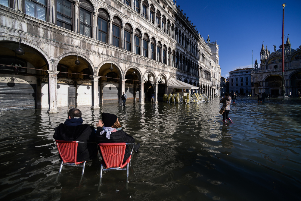 People sit on bistro chairs in the middle of the flooded St Mark's Square November 14, 2019 in Venice. — AFP pic