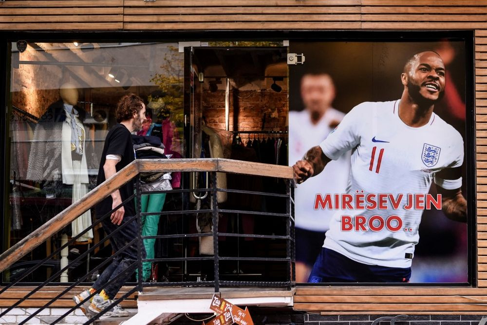 A man walks next to a banner picturing England's forward Raheem Sterling and reading 'Welcome Bro' displayed on the facade of a clothing store, in Pristina on November 13, 2019. — AFP pic