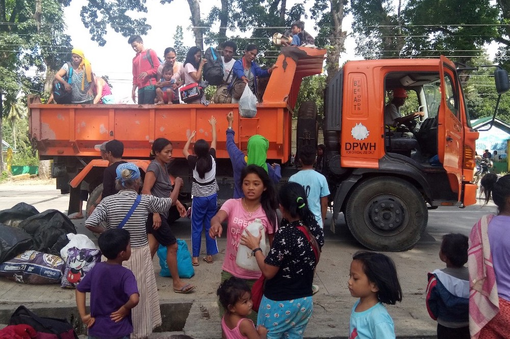 Residents, whose village were affected by a landslide due to a 6.5-magnitude earthquake, disembark from a government truck at a school compound in Makalila town, north Cotabato province, on November 1, 2019. — AFP pic