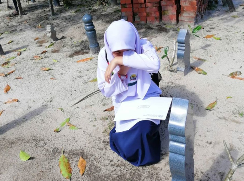 Nur Aqilah Afiah Muhammad Firdaus refused to open the envelope that contained her results until she reached her mother's grave. — Picture from Facebook/Aishah Mat Akat