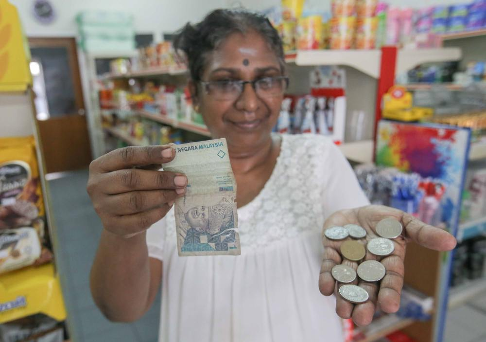 Grocery shop owner Magheswary Pitchay shows the damaged notes and also foreign coins she received from customers.