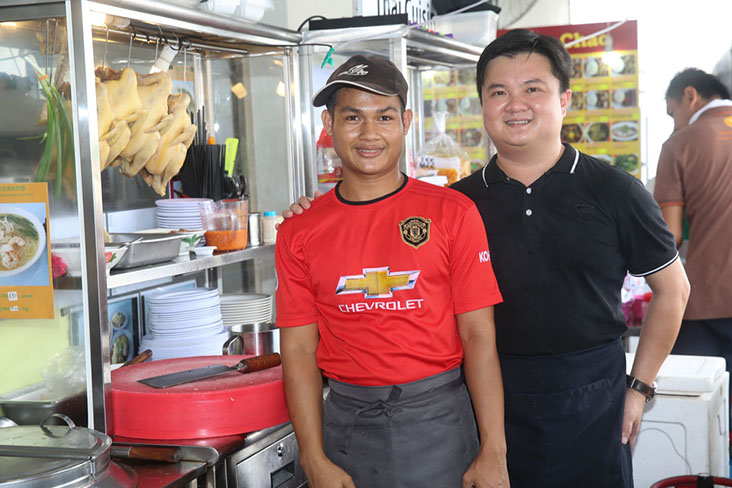 Brodsky Chong (right) with Thet Naing (left) who helps him at his stall that sells 'kai see hor fun' and chicken rice