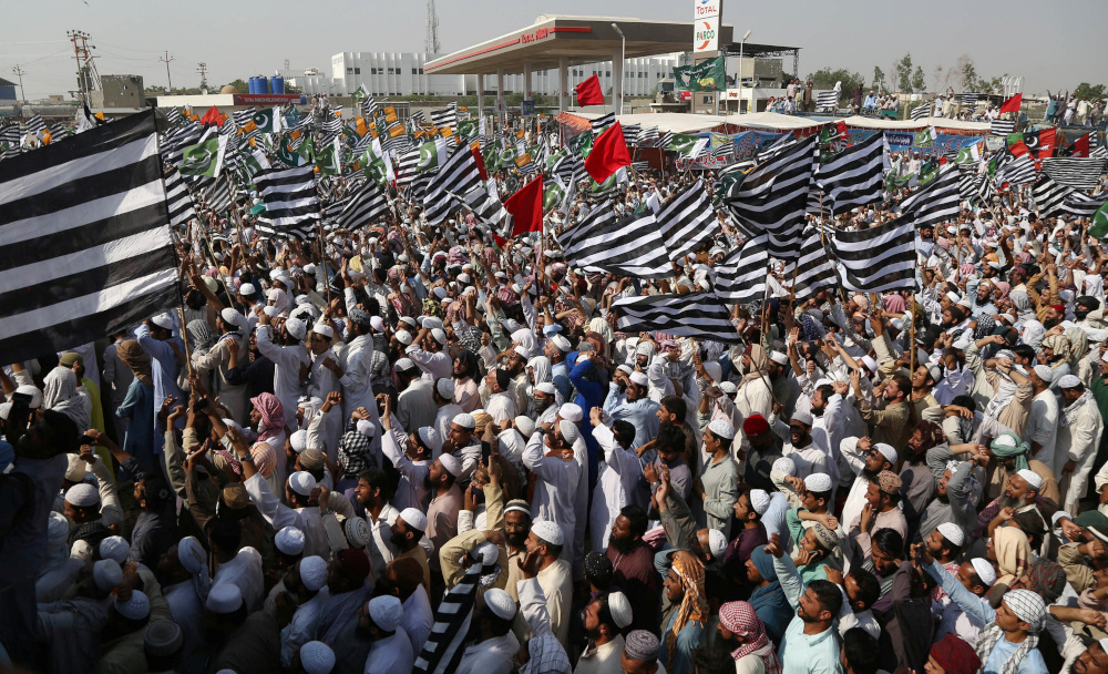 Supporters of religious and political party Jamiat Ulema-i-Islam-Fazal (JUI-F) wave flags as they listen to the speech of their leaders while heading towards Islamabad city, in Lahore October 30, 2019. — Reuters pic