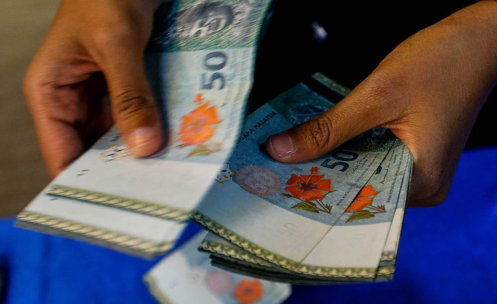 A teller counts RM50 notes in George Town November 27, 2019. ― Picture by Sayuti Zainudin