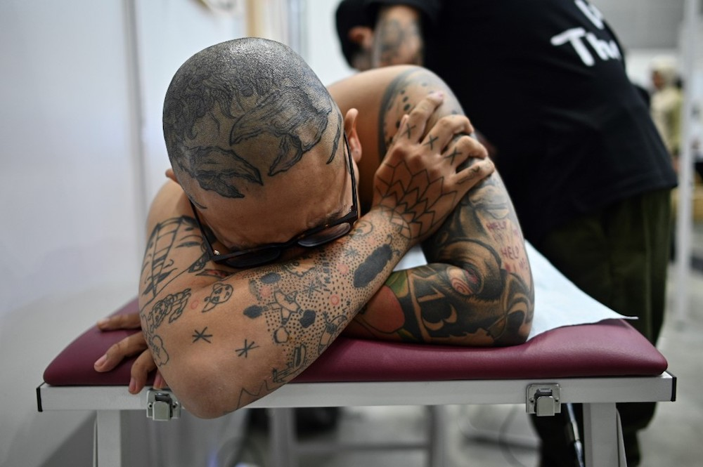 A client lies on a bed while a tattoo artist works during the Tattoo Malaysia Expo 2019 in Kuala Lumpur November 29, 2019. — AFP pic