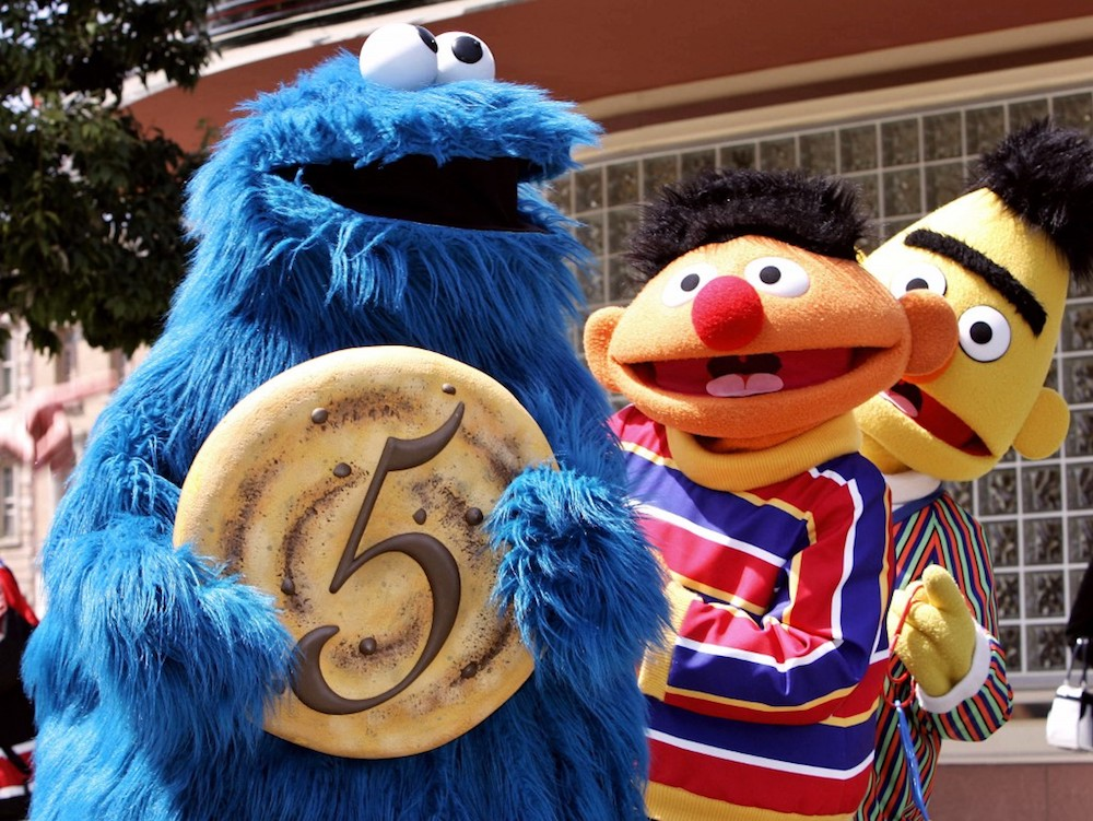 'Sesame Street' character Cookie Monster shows a large cookie with the figure five to celebrate the fifth anniversary of Hollywood theme park Universal Studios Japan in Osaka April 20, 2006, while Ernie and Bert smile. — AFP pic