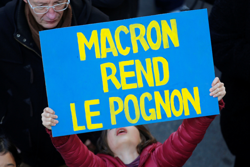 A child holds a placard during a demonstration against French government's pensions reform plans in Marseille as part of a second day of national strike and protests in France, December 10, 2019. The slogan reads 'Macron, return the money'. — Reuters pic