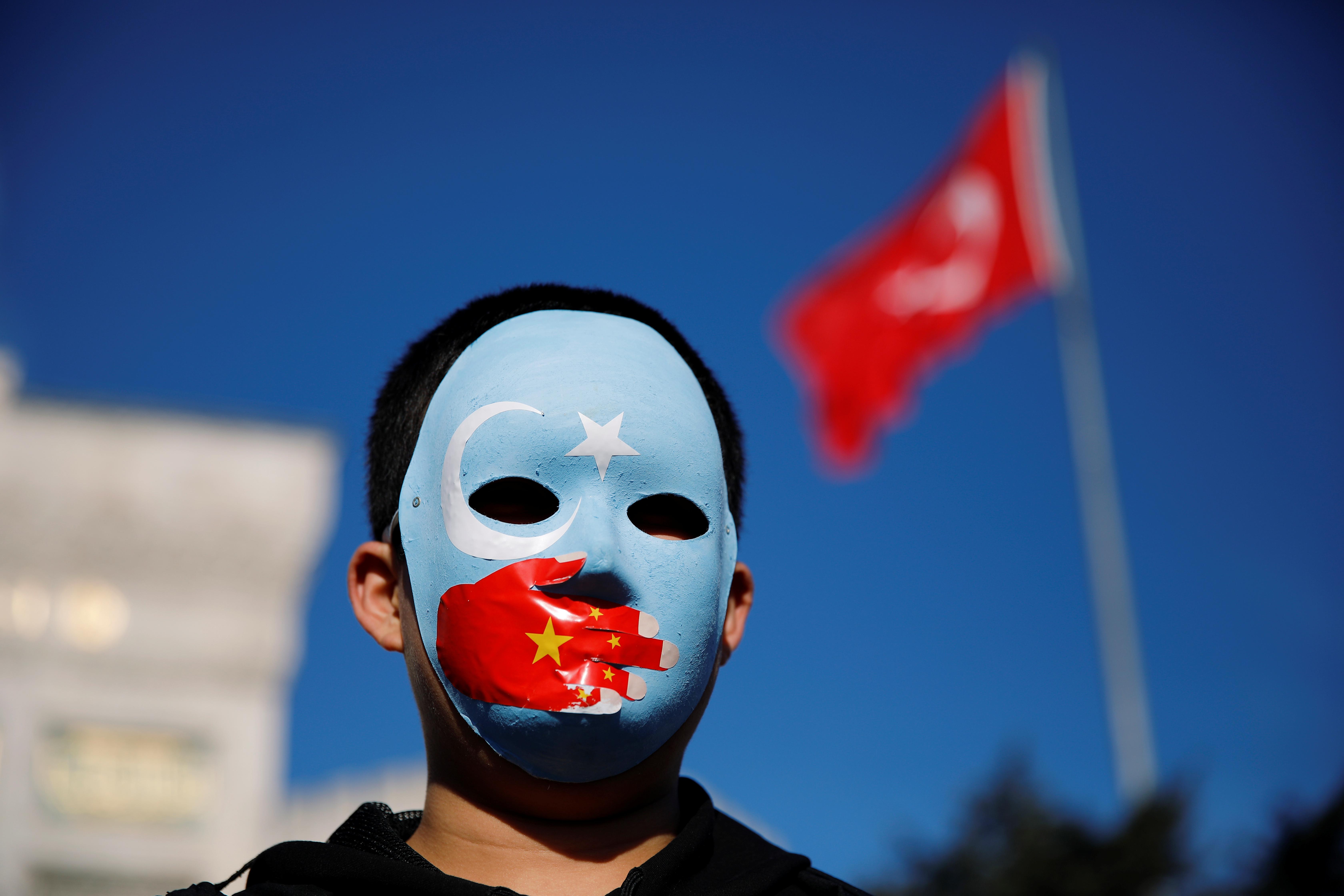 土耳其伊斯坦堡的维吾尔人戴上象征疆独的东突厥斯坦旗帜的面具,抗议中国政府打压维吾尔族人权。-路透社-