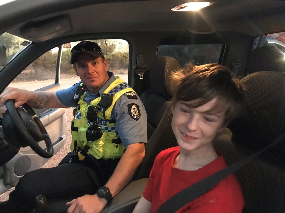 A 12-year-old boy sits next to Dalwallinu Police officer S/C Smith after he drove across paddocks to escape the fire in Mogumber, Australia December 15, 2019 in this picture obtained from social media. — Picture via Twitter/Dalwallinu Police