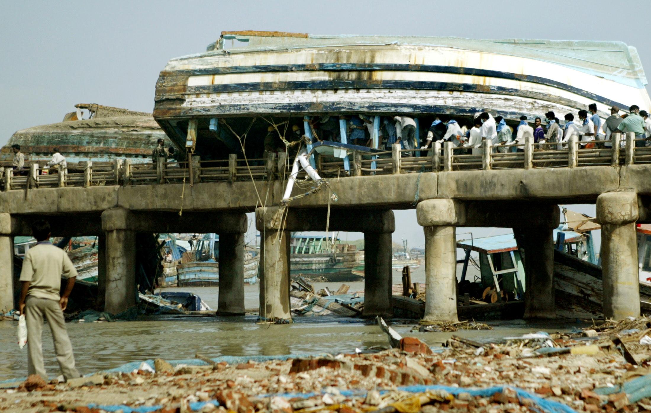 2004年12月26日印度洋大海啸,1天内造成23万人死亡。图示当时一艘拖网渔船被大浪冲上印度的纳加伯蒂讷姆港口。-路透社-
