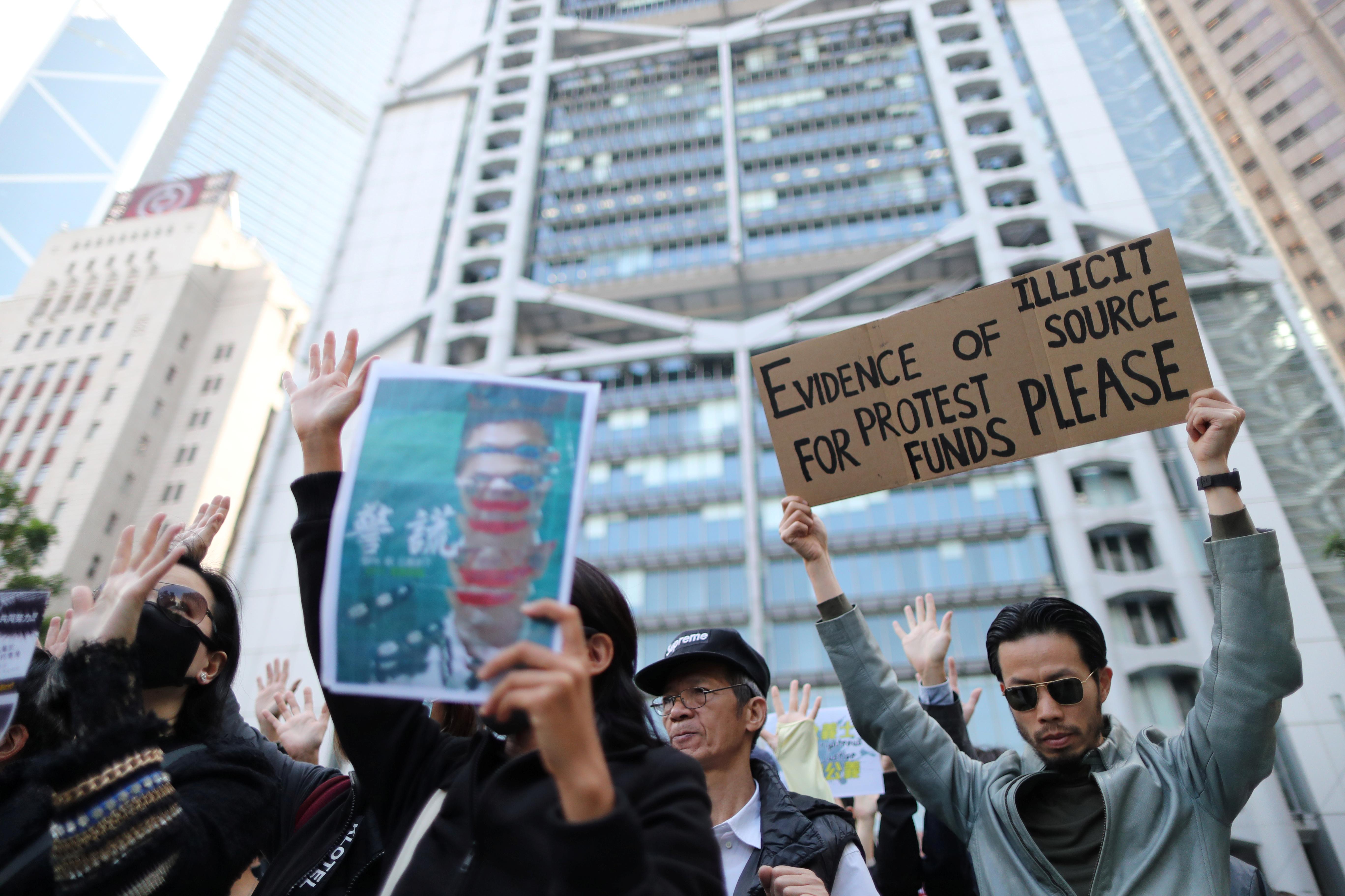 """近百人周五趁午饭时间在中环皇后像广场聚集并高叫口号,不少人举起标语声援""""星火同盟"""",质疑港府打压维权组织。-路透社-"""
