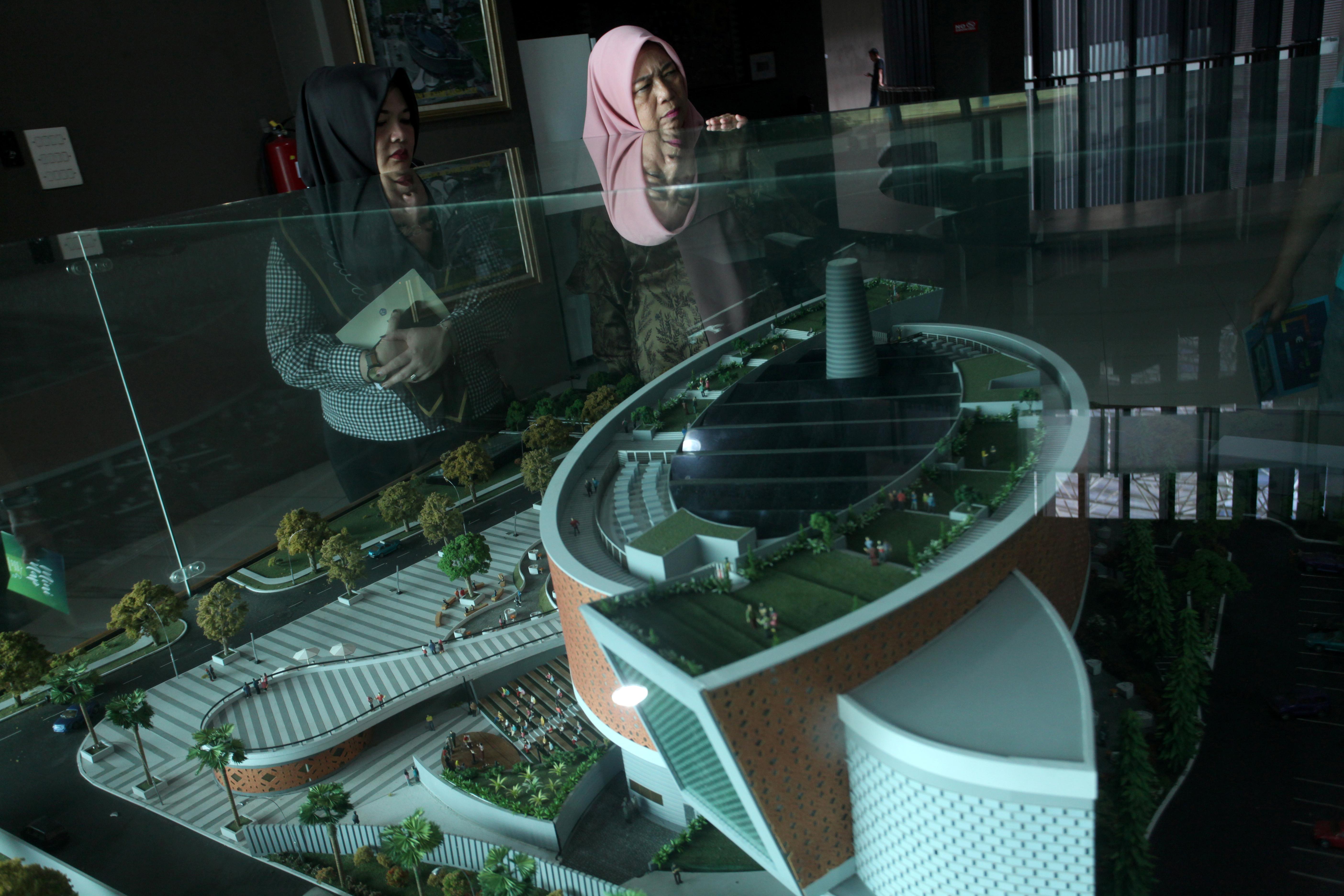 游客观看亚齐海啸博物馆的模型。该博物馆坐落在班达亚齐的一座山上,既是一个教育中心,也是一处避难之地。-路透社-