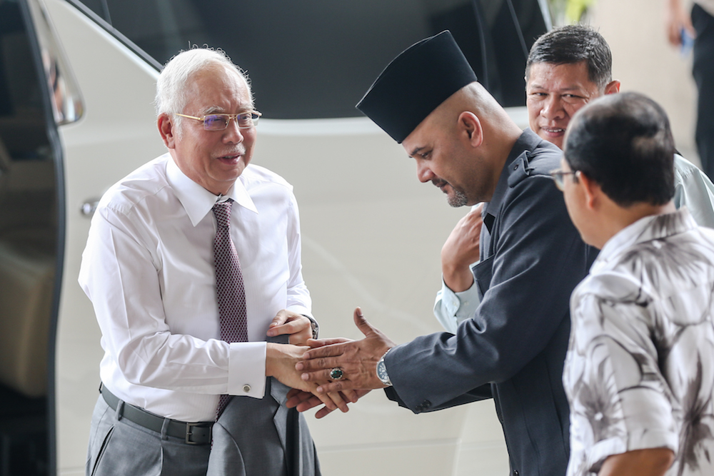 Former prime minister Datuk Seri Najib Razak is greeted by a supporter at the Kuala Lumpur High Court December 9, 2019. — Picture by Firdaus Latif
