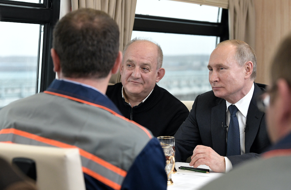 Russian President Vladimir Putin listens to construction workers as he travels by train from Kerch to Taman across a bridge December 23, 2019. — Reu