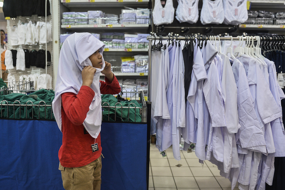 Parents purchase necessities for their children in Subang Jaya December 25, 2019, ahead of the new school year. — Picture by Miera Zulyana