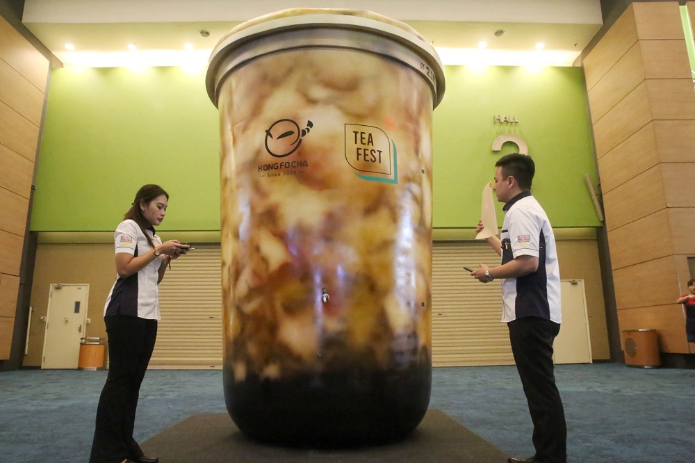 Malaysia Book of Records representatives Nurul Fatihah Mahmood (left) and Jwan Heah pictured with the boba model cup. — Picture by Choo Choy May