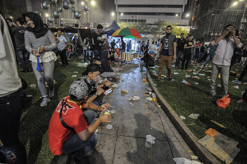 Seen here are those celebrating New Year's Day in KLCC, with rubbish strewn all over the ground. January 1, 2018 — Picture by Miera Zulyana
