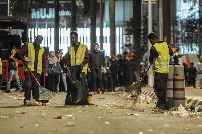 Cleaners are seen sweeping away the rubbish thrown along the road by those celebrating New Year's Day in KLCC. January 1, 2018 — Picture by Miera Zulyana