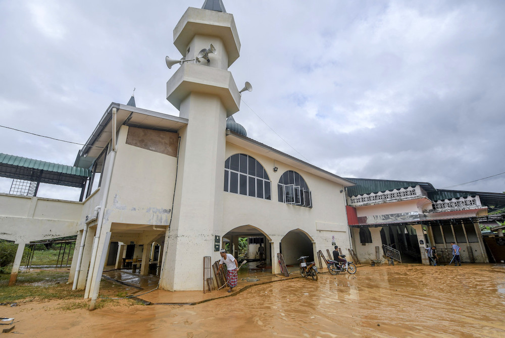 People carry out a clean-up operation at a mosque in Kampung Chenulang in Kuala Krai November 30, 2019, after it was inundated with floodwater. — Bernama pic