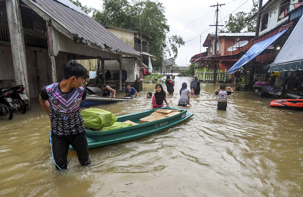People use a sampan to transport goods along a flooded street in Rantau Panjang, Pasir Mas December 1, 2019. — Bernama pic
