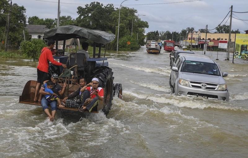 Vehicles travel along a flooded street in Pasir Mas December 2, 2019. — Bernama pic