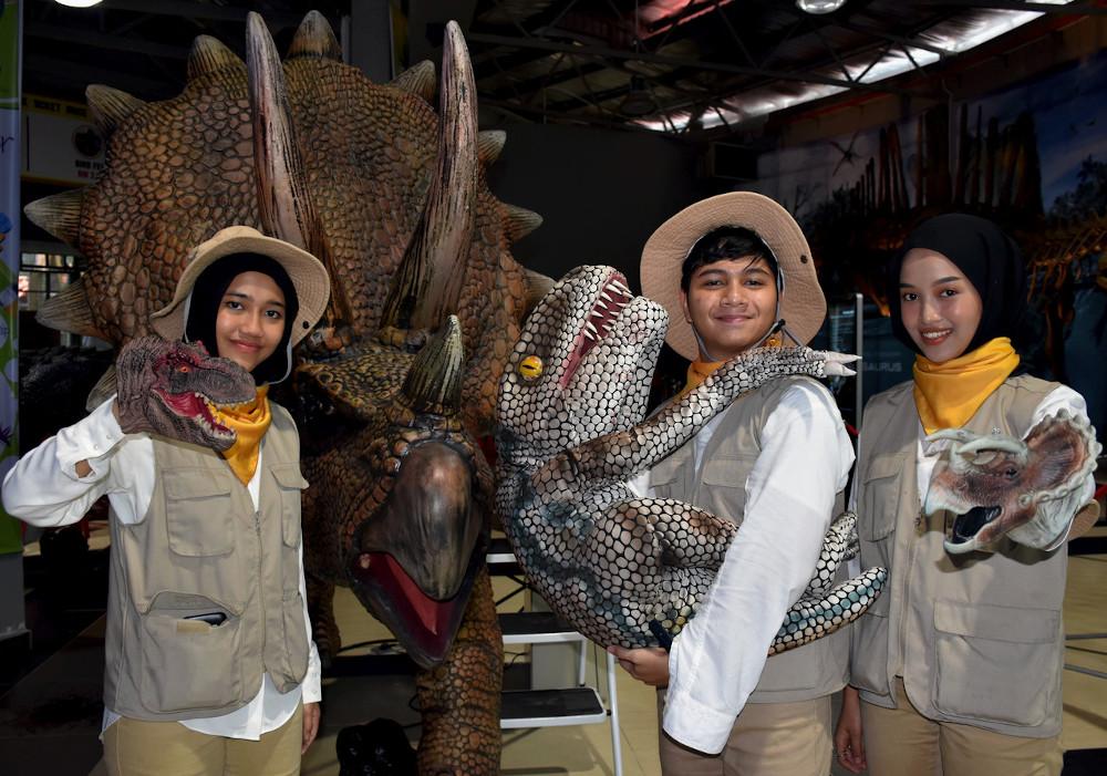 (From left) Rangers Alia Syazwina Mior Salim, Adam Abdul Latiff dan Nurul Shahida Shamsudin pose with dinosaur models at the Melaka Bird Park in Melaka December 15, 2019. — Bernama